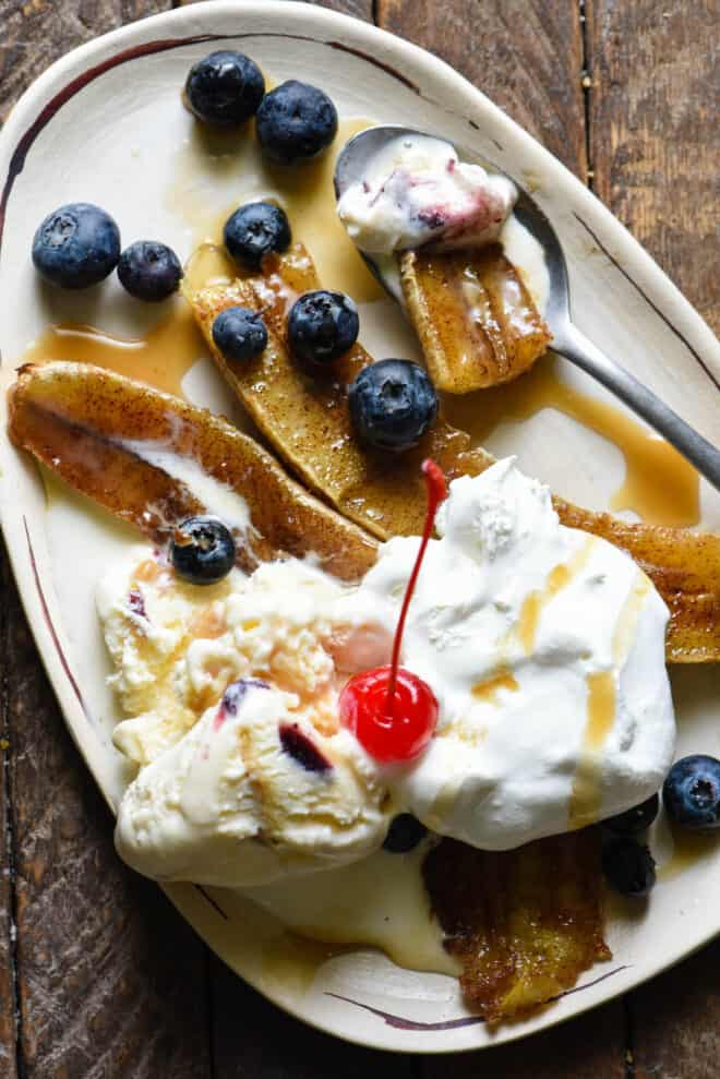 Small oblong shaped white plate topped with a broiled banana, ice cream, blueberries, caramel sauce and a cherry.