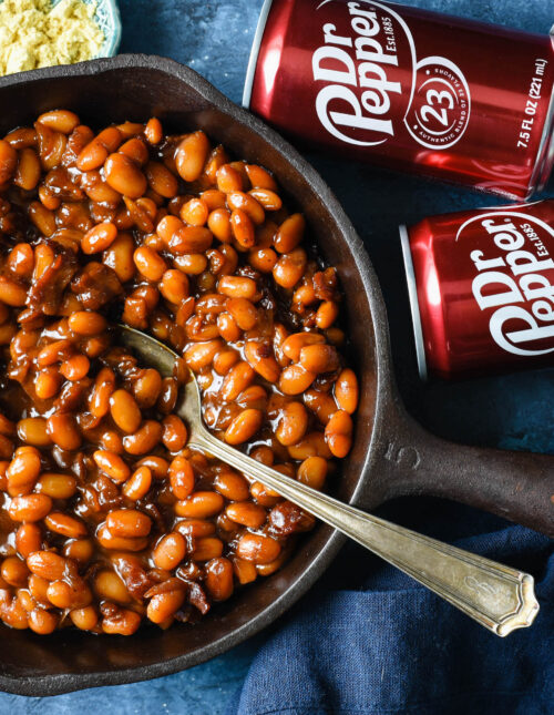 Cast iron skillet filled with baked beans with cans of Dr. Pepper next to skillet.