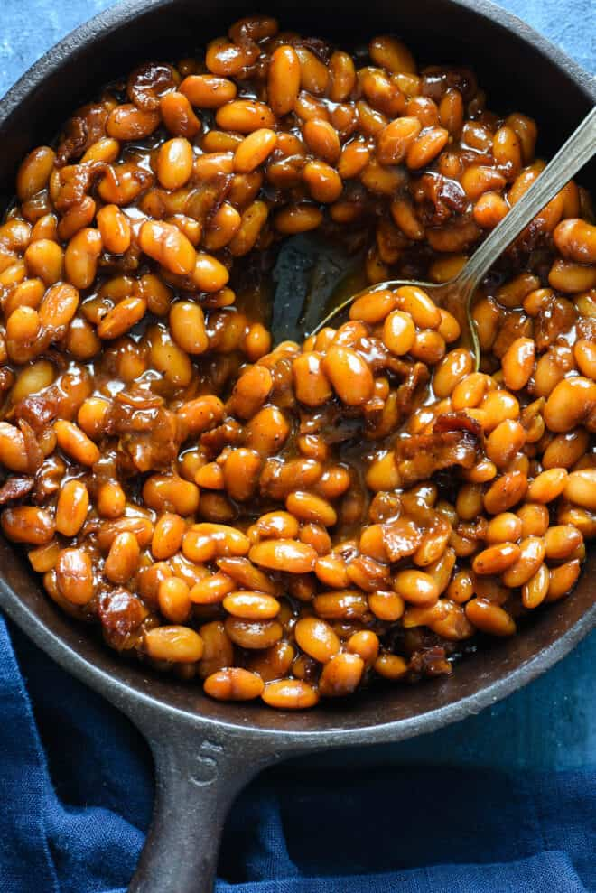 Cast iron skillet filled with Dr. Pepper baked beans, with spoon dishing out some beans.