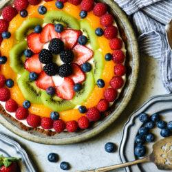 Frozen yogurt pie topped with artfully arranged fruit on a light gray background.