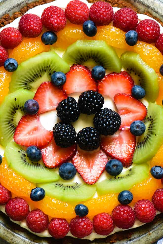 Closeup on creamy tart with artfully arranged berries, kiwi and oranges on top.