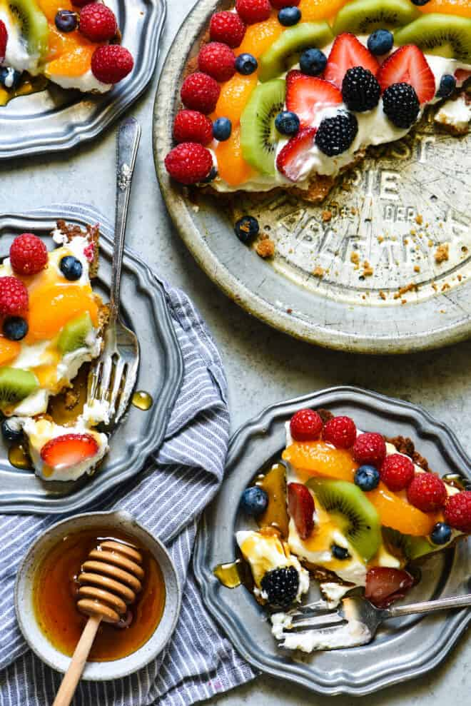 Antique pie pan with half of a creamy pie topped with fruit, alongside plates with pie slices topped with honey.