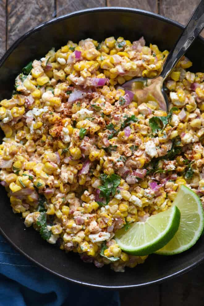 Corn dish with cheese and red onions in a black bowl, garnished with lime wedges.