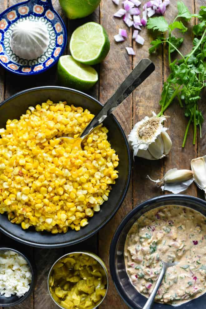 Ingredients for elote salad on a wooden surface, including corn kernels, creamy sauce, feta cheese, chopped red onion and garlic.