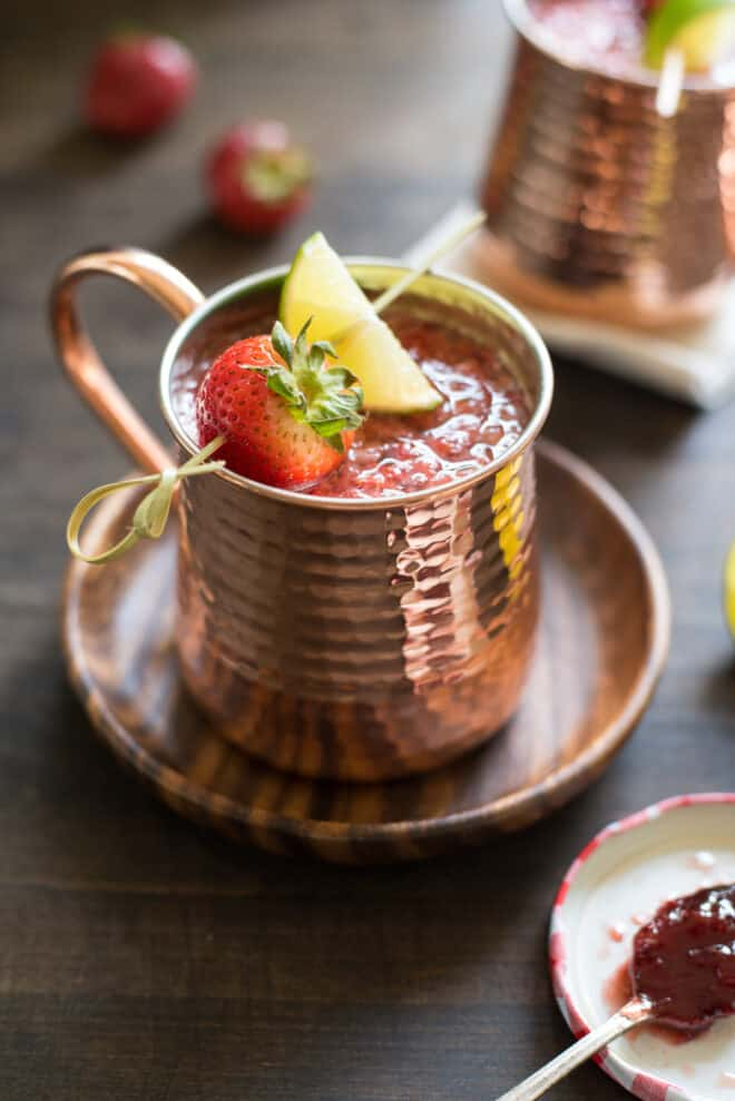 Hammered copper mug filled with strawberry Moscow mule, garnished with a skewer with a strawberry and lime wedge. Mug is resting on small wooden plate.