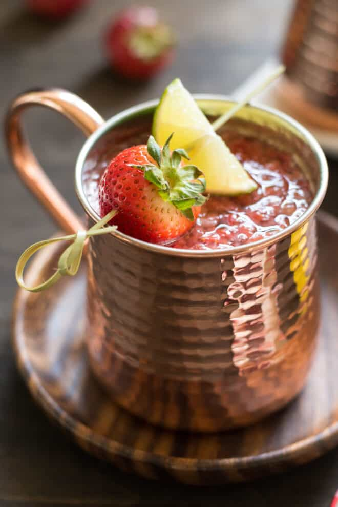 Hammered copper mug filled with strawberry Moscow mule, garnished with a skewer with a strawberry and lime wedge.