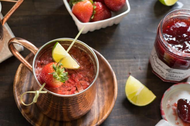 Strawberry cocktail in a copper mug with a skewer of strawberry and lime resting on top of mug.