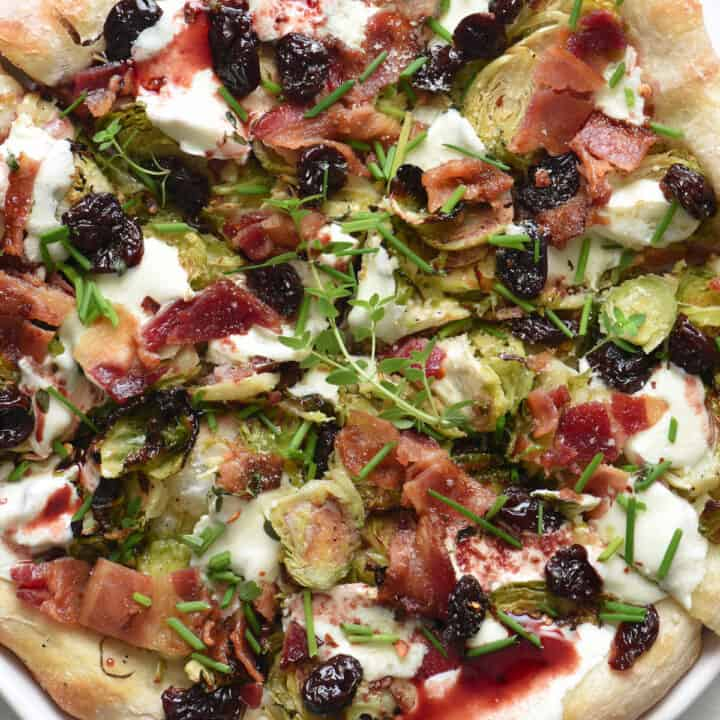 A rustic looking pizza, with Brussels sprouts on pizza, along with bacon, herbs and cherry glaze.