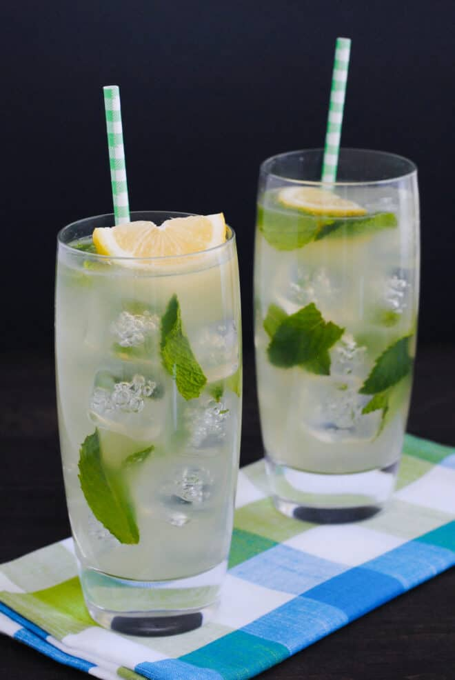 Two tall glasses of mint honey drink over ice, garnished with paper straws and lemon wedges.