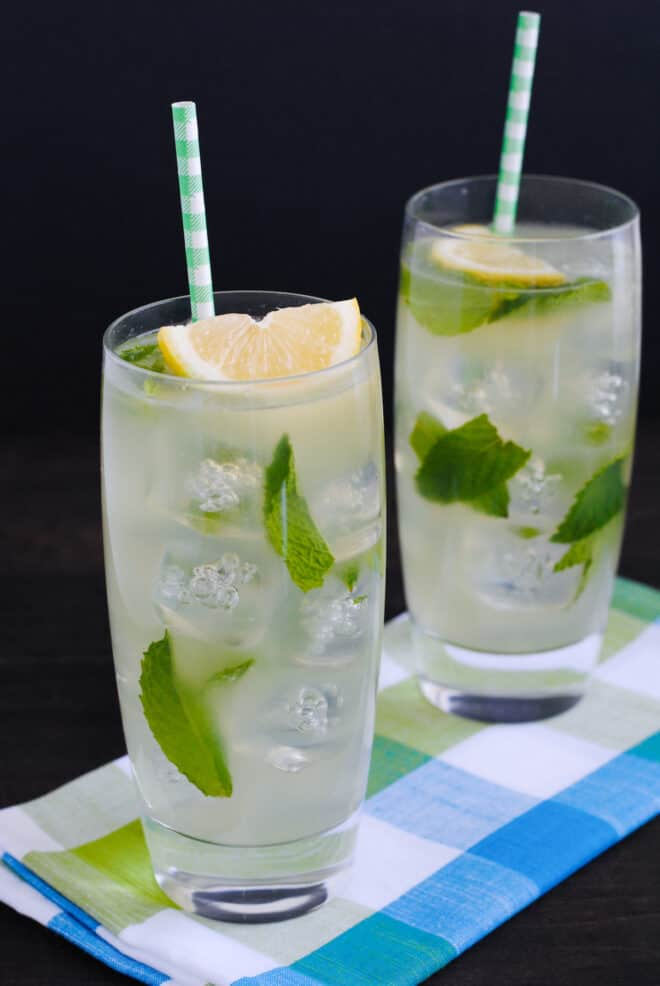 Two tall glasses of lemon drink garnished with lemon wedges, mint leaves and paper straws.