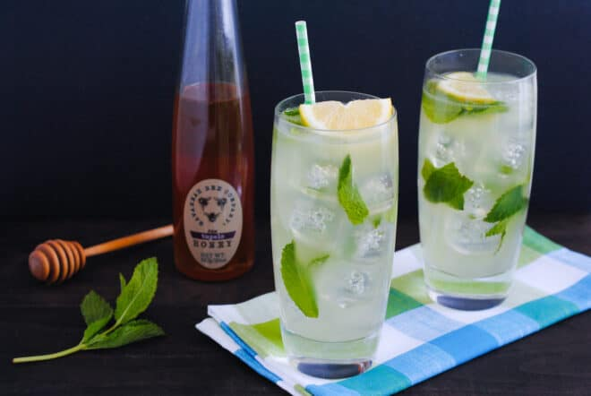 Two tall glasses of lemon mint drink with a bottle of honey and honey dripper in background.