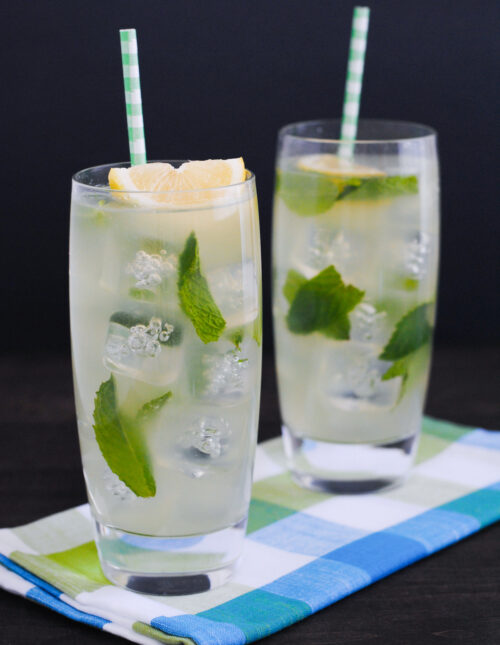Two tall glasses filled with ice, honey lemonade, mint leaves, lemon wedges and paper straws.