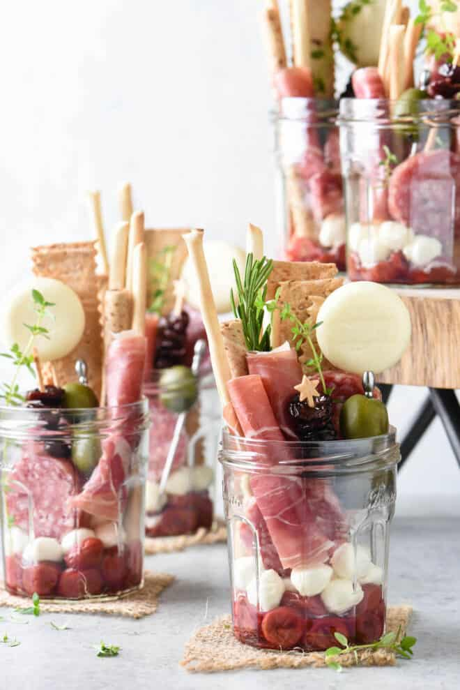 Glass jars filled with charcuterie, cheeses, fruits and crackers.