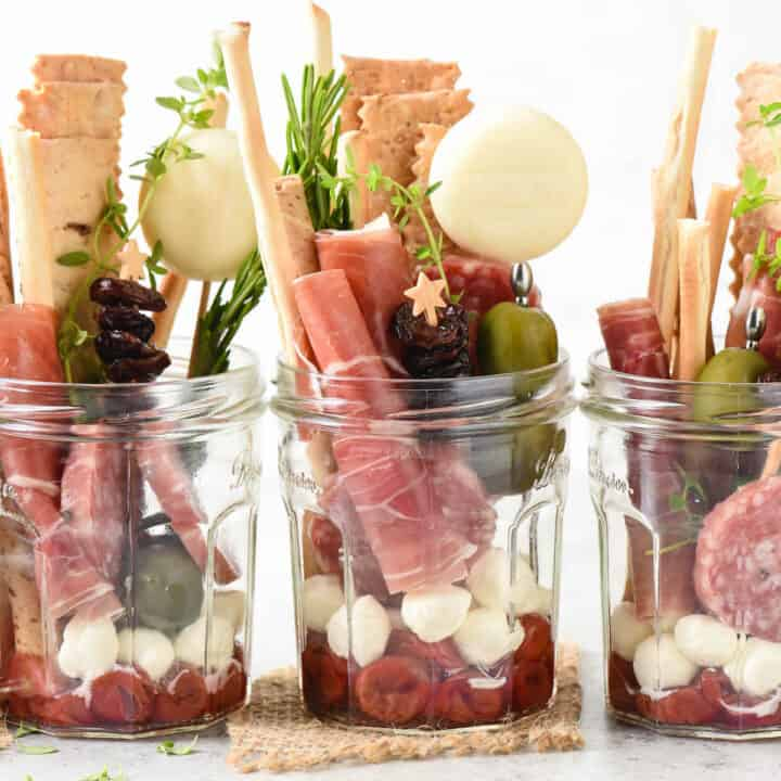 Five servings of jarcuterie, which are glass jars filled with charcuterie, cheese, crackers and condiments.