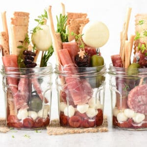 Glass jars filled with pickled cherries, charcuterie, cheese and crackers.