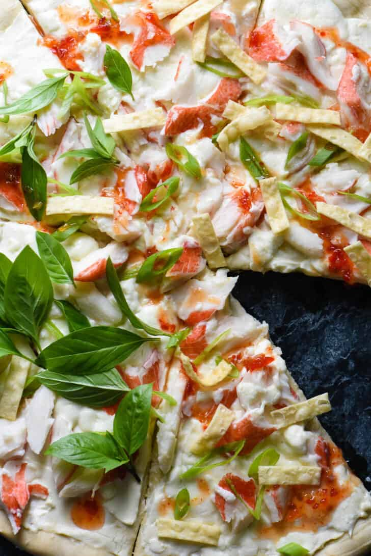 Pizza crust topped with cream cheese, imitation crab, green onions, wonton strips and basil.