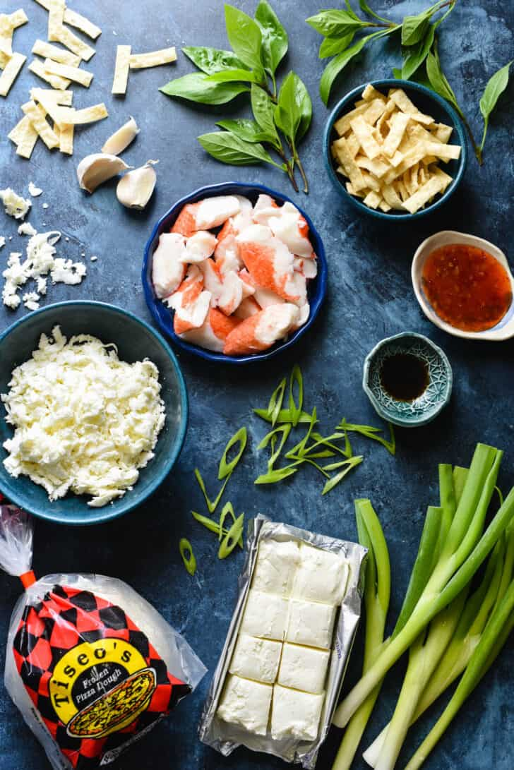 Ingredients needed for crab rangoon pizza, including pizza dough, cream cheese, green onions, mozzarella cheese, imitation crab, wonton strips, garlic, Worcestershire sauce and sweet chili sauce.