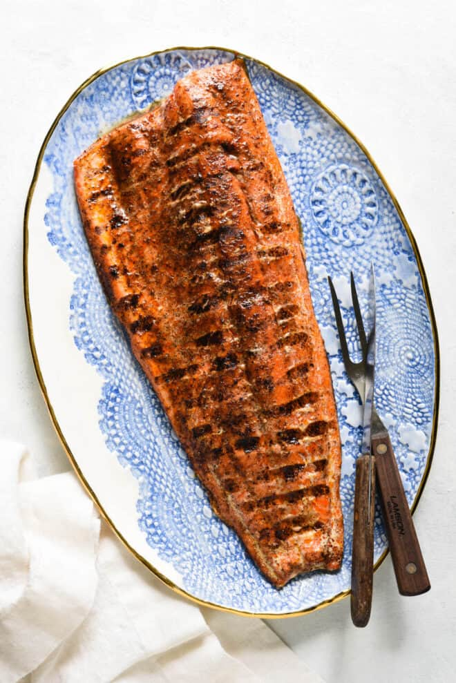 Decorative blue and white platter topped with large piece of grilled sockeye salmon.