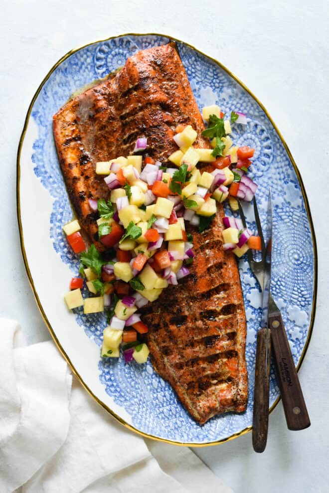 Decorative blue and white platter topped with a large piece of grilled fish with skin and chopped pineapple salsa.