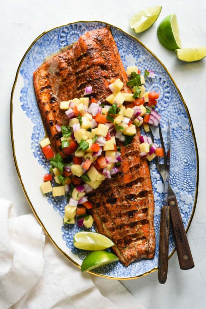 Decorative blue and white platter topped with a large piece of grilled salmon with skin and chopped pineapple salsa.