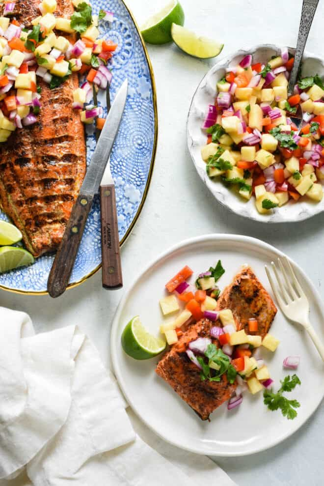 Meal scene featuring a platter and a smaller plate of salmon with pineapple salsa being served.
