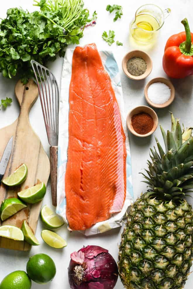 Flat lay of ingredients needed to make grilled sockeye salmon and pineapple salsa, including fruit, herbs and spices.