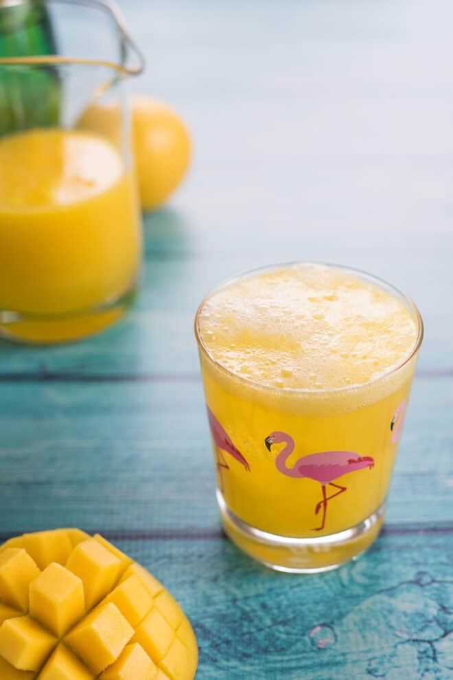 Glass with flamingo printed on it on teal table, filled with an orange hued beverage.