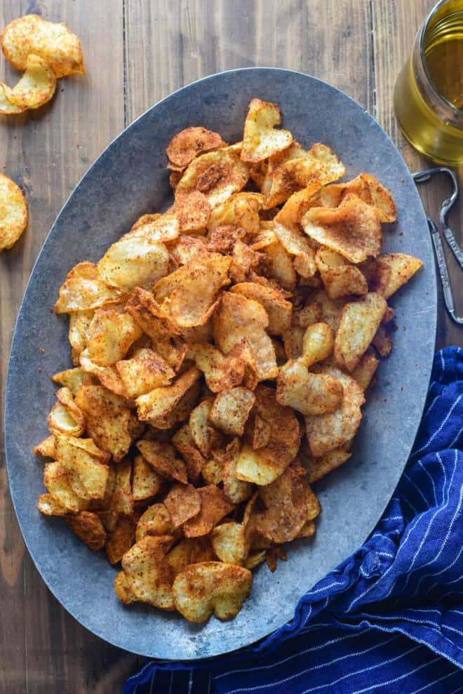 Oval metal plate topped with spicy chips.