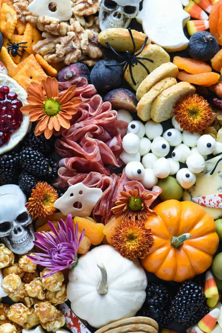 Easy charcuterie board made with salami, mini mozzarella cheese, blackberries and dried apricots. Pumpkins and fall flowers decorate the tray.