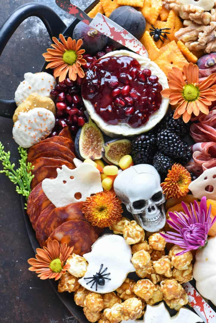 Halloween cheese board made with French cheese round topped with red jam, pumpkin cookies, pepperoni, crackers, walnuts, figs, and spooky decorations.