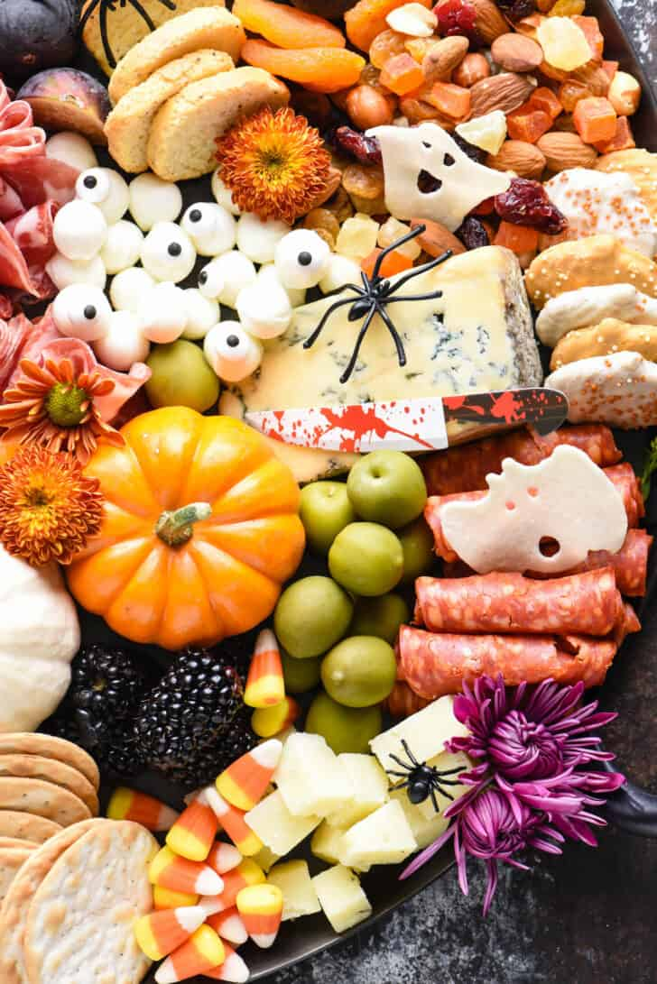 Spooky appetizer tray made with blue cheese, mini mozzarella balls, crackers, olives, mini pumpkins, cookies and trail mix. Plastic spiders on cheese.