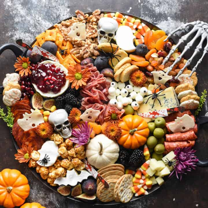 Halloween charcuterie board filled with cheeses, meats, pumpkins, crackers, nuts, fruits and sweets.