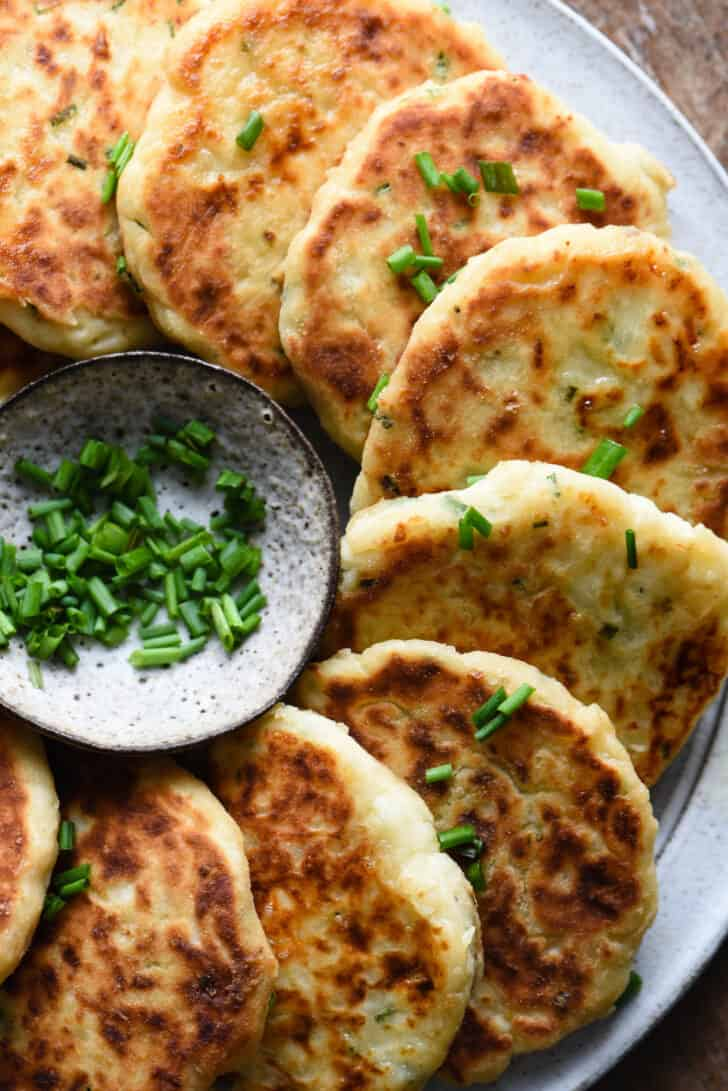 Potato cakes arranged in a semi circle near a small bowl of sliced chives.