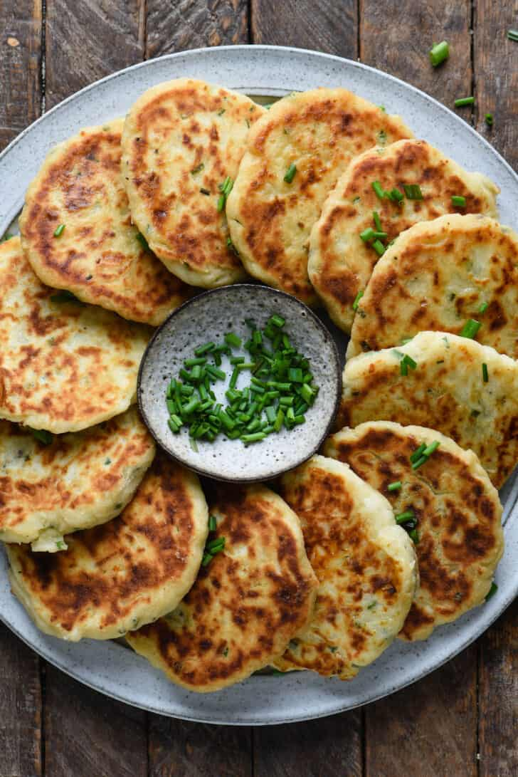 Gray plate topped with mashed potato cakes arranged in a circle, with a small bowl of chives in center of circle.