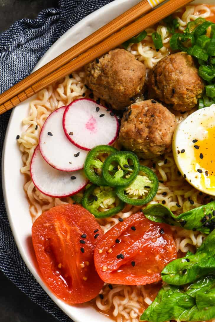 Tomato ramen noodles topped with meatballs, egg, radishes, jalapeno peppers, tomatoes and black sesame seeds.