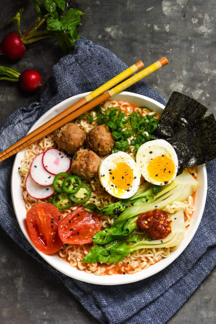 Ramen noodles with tomato broth in a white bowl, topped with meatballs, a soft boiled egg, and a variety of vegetable garnishes.