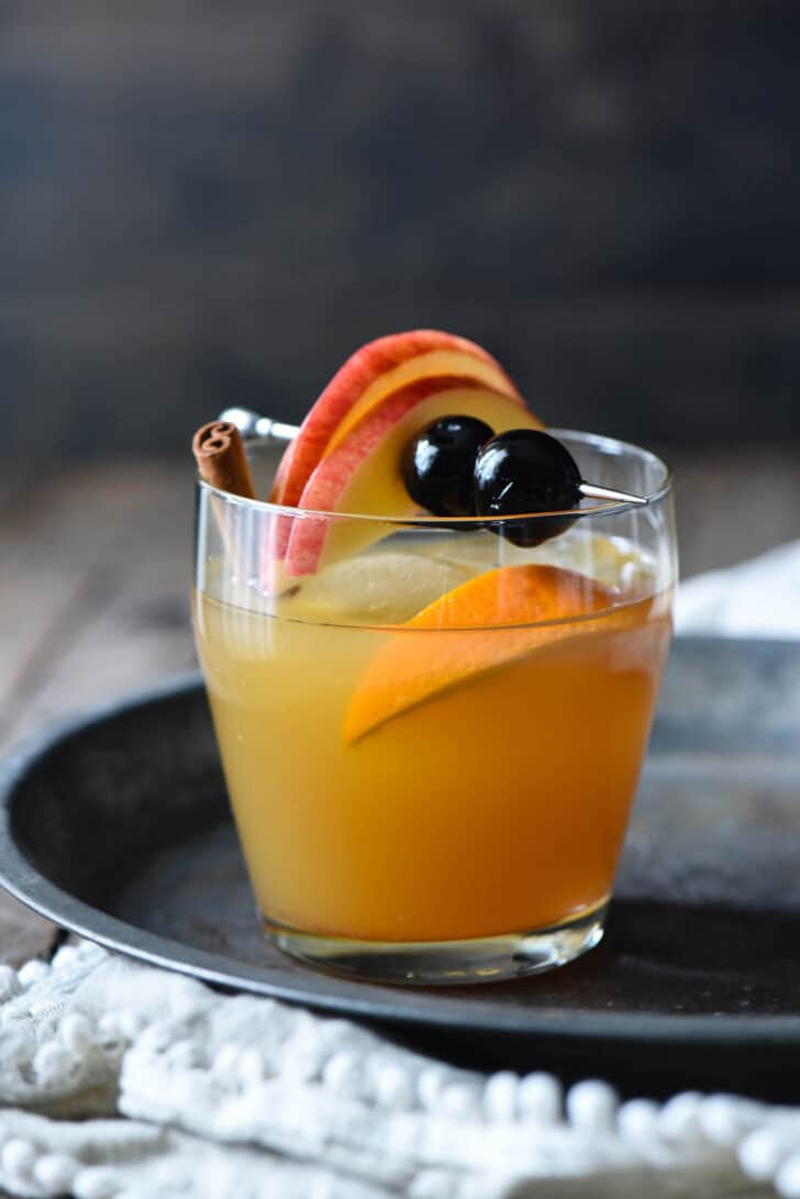 An apple cider bourbon cocktail in a small glass, garnished with an orange slice, cinnamon stick, and metal skewer with apple slices and cocktail cherries.