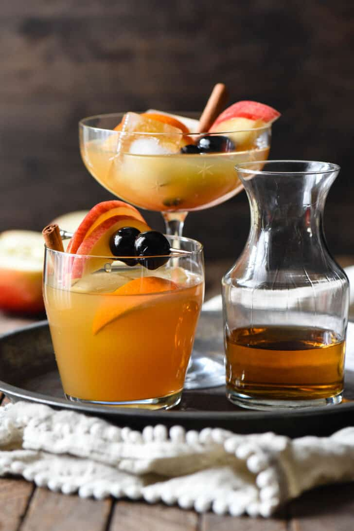 A tray of apple cider and whiskey drinks in various glasses, with a carafe of whiskey as well.
