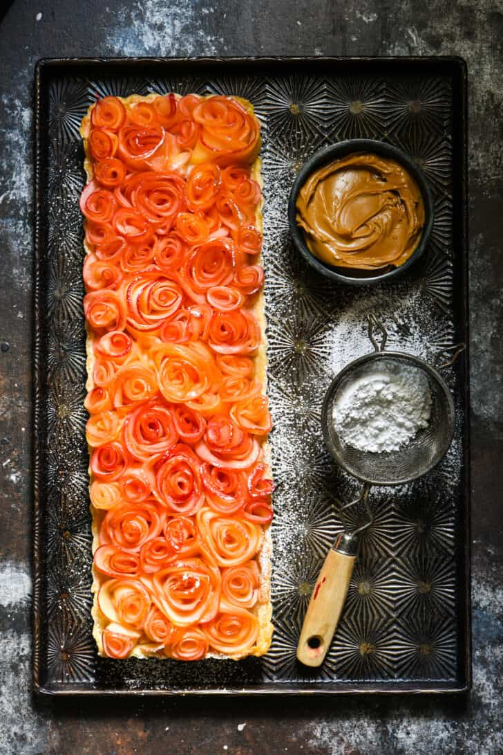 """Rectangular tart topped with apple """"roses"""" on vintage baking pan with bowl of peanut butter and powdered sugar sifter."""