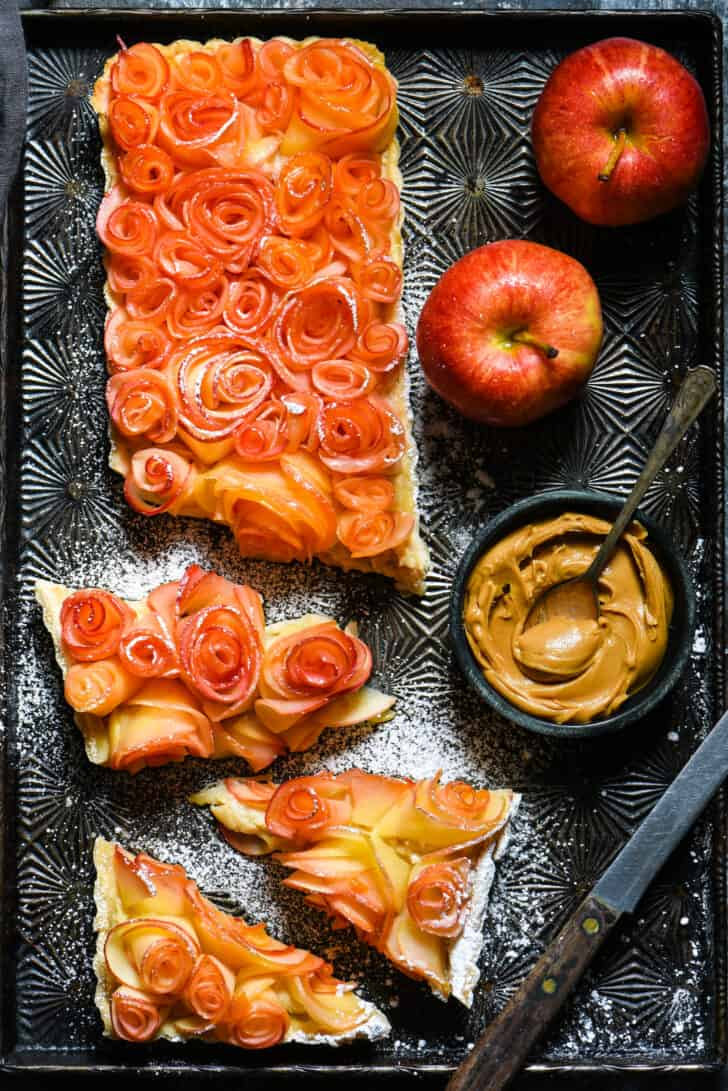 Apple tart made with decorative roses made from apples, cut into pieces on vintage baking pan, with bowl of peanut butter and fresh apples nearby.
