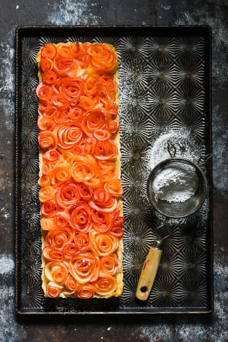 Long rectangle apple rose tart on vintage baking pan with powdered sugar sifter.