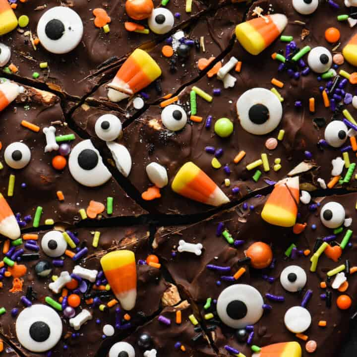 Halloween bark made from chocolate, sprinkles, candy corn and candy eyeballs, broken into pieces, on dark surface.