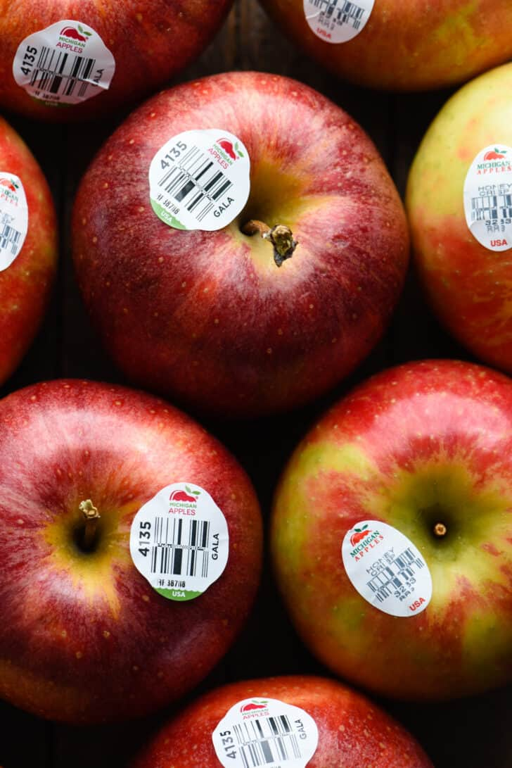 A closeup photo of several red apples with Michigan Apples bar code stickers on them.
