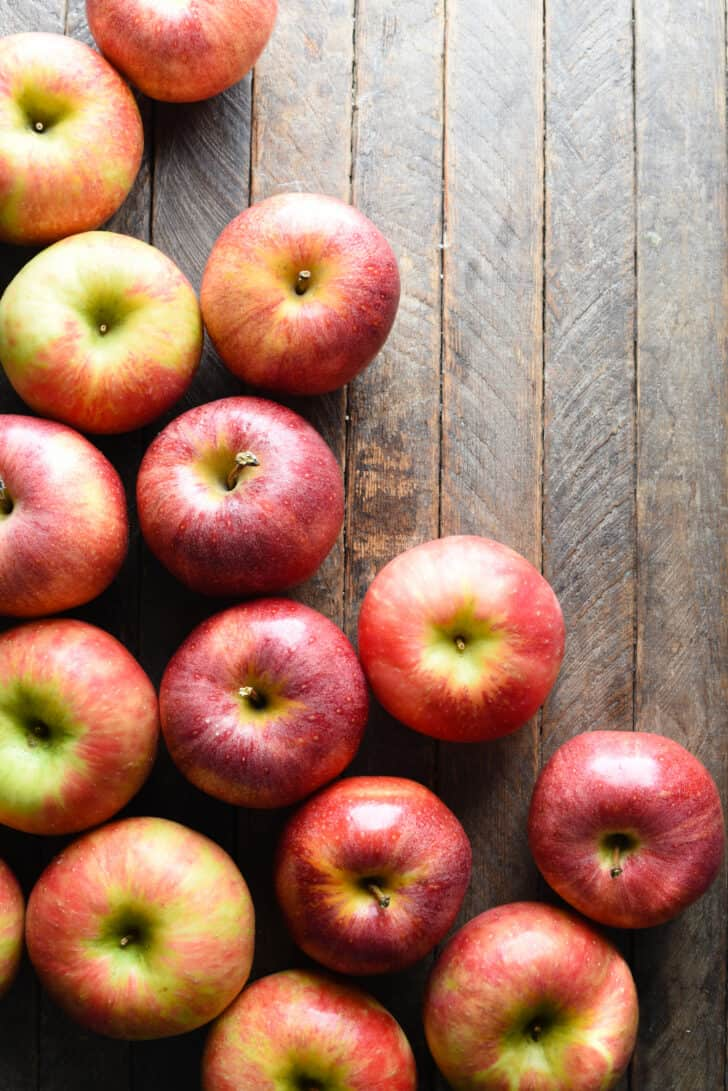 A dozen or so red apples on a planked wooden table, shot from above.