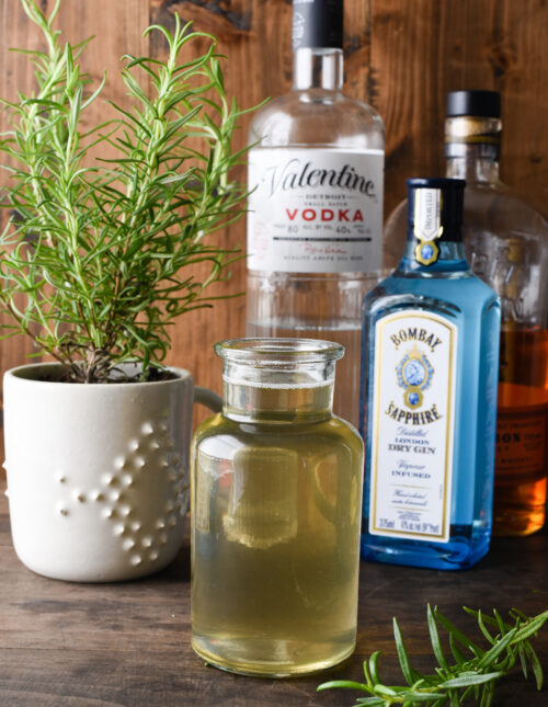 Small bottle of rosemary simple syrup with liquor bottles and rosemary plant in background.