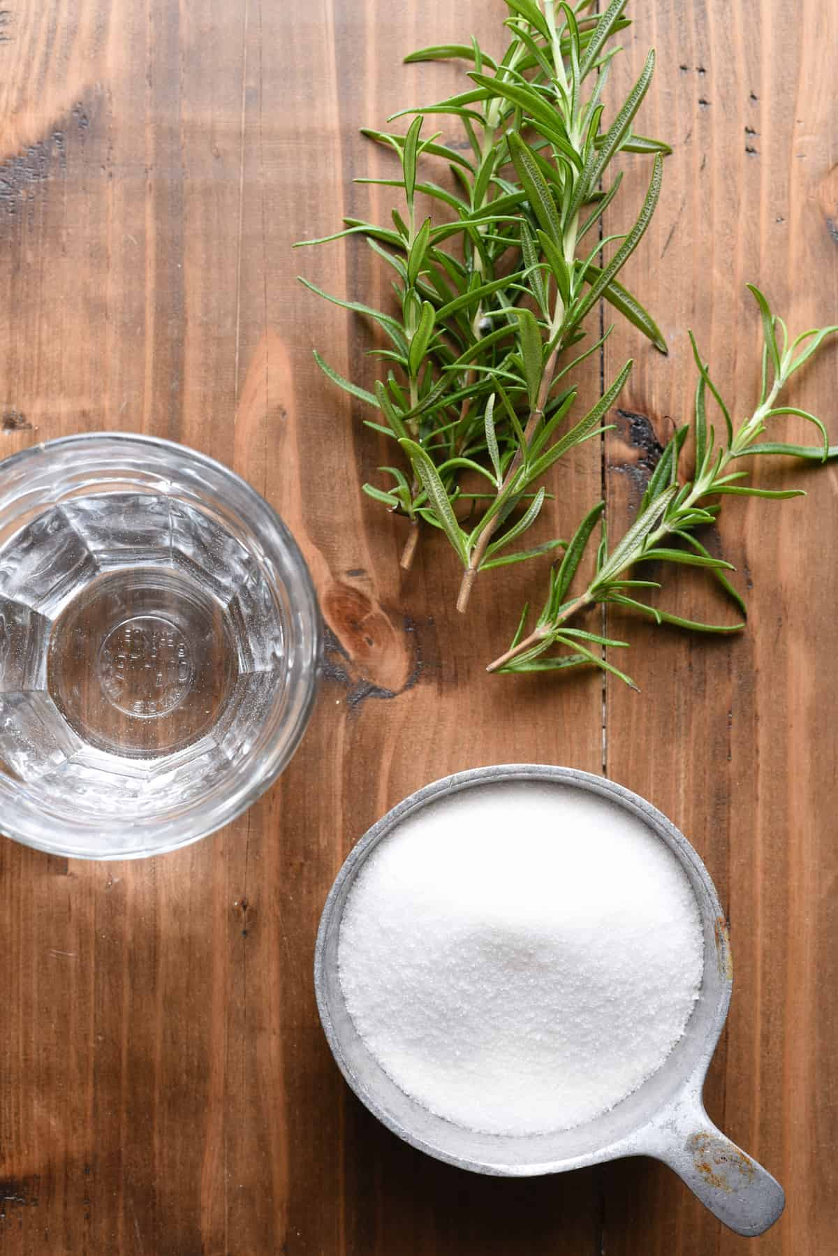 Overhead photo of cup of sugar, glass of water and rosemary sprigs on wooden table.