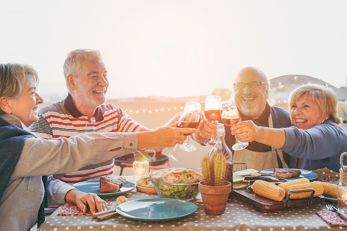 Group of elderly friends eating food and drinking wine together.