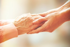Elderly person and young carer holding hands