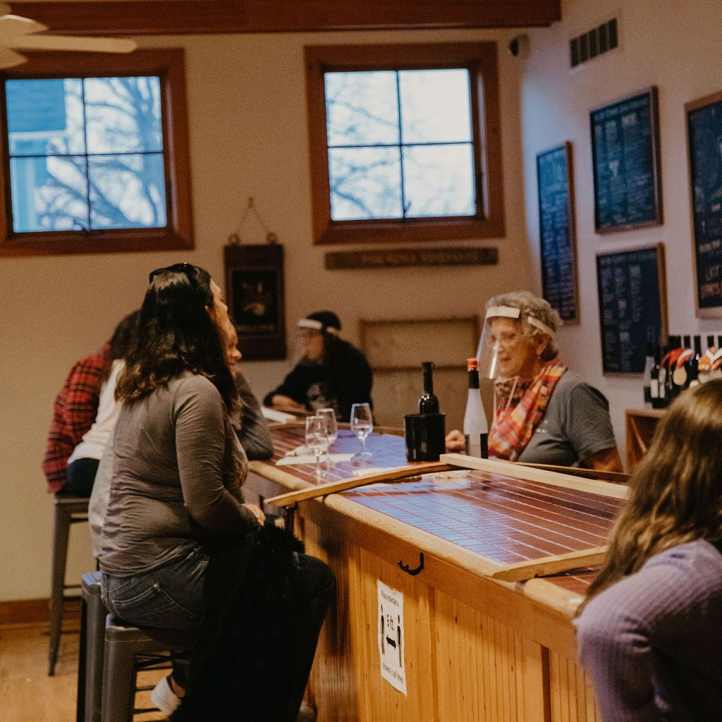 Staff serving seated customers at the tasting bar
