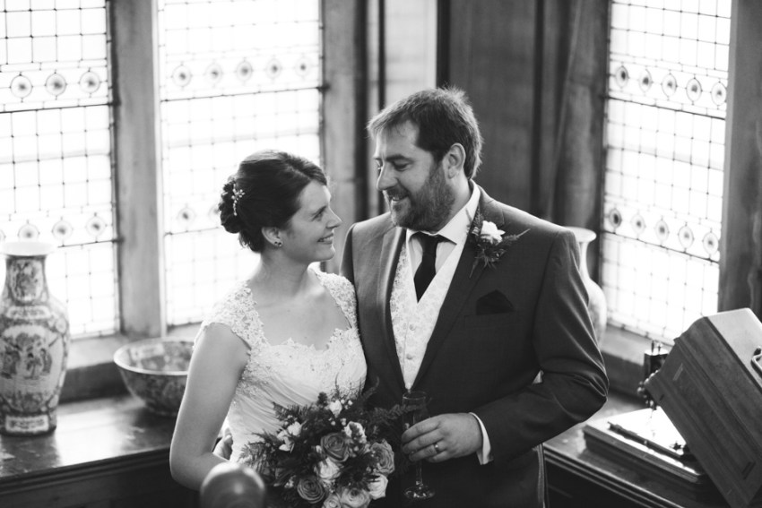 Simonstone Hall wedding photography of the bride and groom in front of stained glass windows